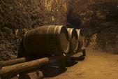 Row of wine tuns on wooden platform underground — Stock Photo