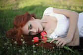 Red-haired girl lying on the grass — Stock Photo