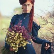 Red-haired girl with a bouquet of wild flowers — Stock Photo