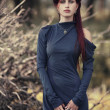 Red-haired girl in a long blue dress in the forest — Stock Photo