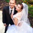 Stock Photo: Bride and groom posing in park