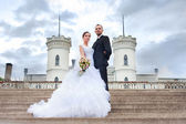 Bride and groom posing near castle — Stock Photo