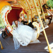 Stock Photo: Beautiful bride and groom riding carousel