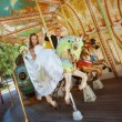 Beautiful bride and groom riding a carousel - Stock Photo