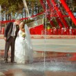 Bride and a groom dance near the fountain — Stock Photo