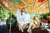 Beautiful bride riding a carousel — Stock Photo