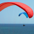 Stock Photo: Red and blue paragliders over the sea
