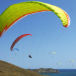 Stock Photo: Few paragliders soar over seshore
