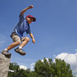 Stock Photo: Boy leaps from rock.