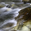 Stream flows over large rock. — Stock Photo