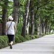 Woman walks along sidewalk. - 图库照片