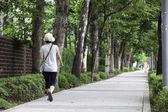 женщина идет вдоль тротуара. — Стоковое фото