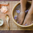 Soaking feet in wooden bowl. — Stock Photo