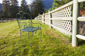 Chair in grass by fence. — Stock Photo