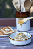 Spoonful of honey on oatmeal. — Stock Photo
