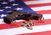 Pistol and ammo on flag. — Stock Photo