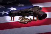 Pistol on flag in the spotlight. — Stock Photo