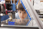 Boy watches machine intently. — Stock Photo