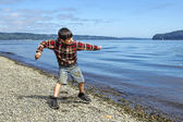 Boy skips a rock in the water. — Stock Photo