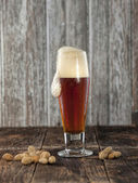 Peanuts and foaming beer. — Stok fotoğraf