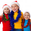 Three happy children in Santa hats — Stock Photo