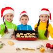 Three smiling kids with Christmas cooking — Stock Photo #12508419