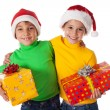 Smiling kids in Santa hats with gift boxes — Stock Photo