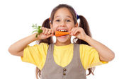 Smiling girl biting the carrot — Stock Photo