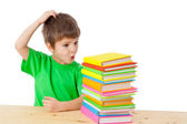 Boy with books scratching his head — Stock Photo