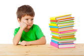 Pensive boy with stack of books — Stock Photo