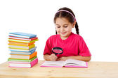 Smiling girl with books and magnifier — Stock Photo