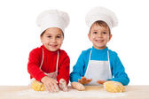 Two kids kneading the dough together — Stock Photo
