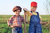 用铁铲在该字段中的两个孩子 — 图库照片