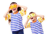 Two funny kids with fruits on eyes — Stock Photo