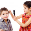 Girl looks to boy's ears through magnifier — Stock Photo
