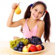 Girl with pear and plate of fruit — Stock Photo
