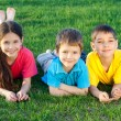 Three happy kids lying on the field - Foto Stock