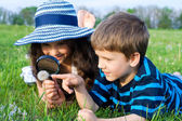 Kids looking to dandelion with a magnifying glass — Stock Photo
