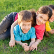 Stock Photo: Three happy kids playing on the meadow