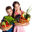 Smiling kids with vegetables in basket — Stock Photo