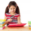 Girl with books and magnifier — Stock Photo