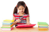 Girl with books and magnifier — Stockfoto