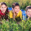 Three smiling kids on the meadow — Stock Photo #35515493