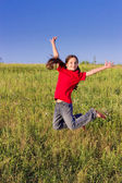 Jumping girl on green field — Stock Photo
