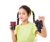Smiling girl drinking jiuce with grape in hands — Stock Photo