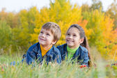Two smiling kids on the autumn meadow — Stock Photo