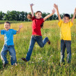Jumping kids on green field — Stock Photo