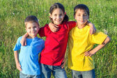 Three smiling kids on the meadow — Stock Photo