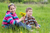 Two kids with dandelions — Stock Photo