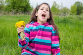 Sneezing girl on meadow with dandelions — Stock Photo